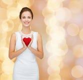 Lächelnde Frau im weißen Kleid mit rotem Herzen Stockfotografie