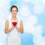 Lächelnde Frau im weißen Kleid mit rotem Herzen Stockbild