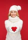 Lächelnde Frau im Winter kleidet mit rotem Herzen Stockfoto