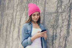 Lächelnde Frau kleidete in der zufälligen Kleidung und rosa im Hut an, die auf der Straßenwand und -anwendung des Internets für p lizenzfreie stockfotos