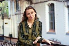 Lächelnde Frau lehnt sich auf dem Geländer Stockfotografie