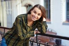 Lächelnde Frau lehnt sich auf dem Geländer Lizenzfreies Stockbild
