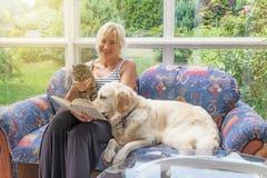 Lächelnde Frau liest ein Buch zusammen mit Haustieren Stockfotos