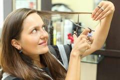 Lächelnde Frau mäht ihr Haar mit Scheren Stockfoto