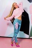 Lächelnde Frau mit afrikanischen Borten in der rosa Strickjacken- und Jeans-Stellung Stockbild