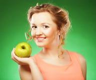 Lächelnde Frau mit Apfel und Stroh-Cocktail, über grünem backgro Lizenzfreies Stockfoto