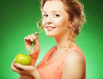 Lächelnde Frau mit Apfel und Stroh-Cocktail, über grünem backgro Stockbilder