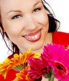 Lächelnde Frau mit Blumen Stockbild