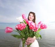 Lächelnde Frau mit Blumenstrauß Meer Stockfotos