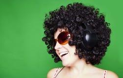 Lächelnde Frau mit dem Afrohaar hören Musik mit Kopfhörern Stockfoto