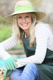 Lächelnde Frau mit dem Hut, der im Garten arbeitet Stockfoto