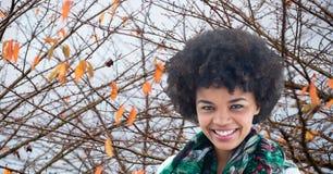 Lächelnde Frau mit dem Kraushaar gegen Herbstniederlassungen Stockfoto