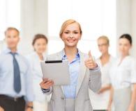 Lächelnde Frau mit dem Tabletten-PC, der sich Daumen zeigt Lizenzfreies Stockfoto