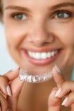 Lächelnde Frau mit den weißen Zähnen, die Zahnweißungs-Behälter halten Lizenzfreie Stockbilder