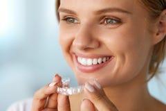 Lächelnde Frau mit den weißen Zähnen, die Zahnweißungs-Behälter halten Stockfoto