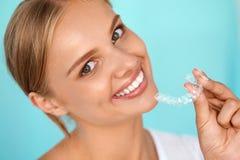 Lächelnde Frau mit den weißen Zähnen, die Zahnweißungs-Behälter halten lizenzfreies stockfoto
