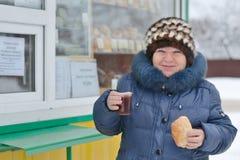 Lächelnde Frau mit einem Brötchen und Tee an einem Straßenrand klemmen fest Stockfotografie