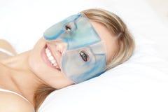 Lächelnde Frau mit einer Augengelschablone stockfotos