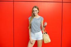Lächelnde Frau mit einer Tasche vor der roten Wand Stockfoto