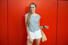 Lächelnde Frau mit einer Tasche vor der roten Wand Lizenzfreies Stockfoto