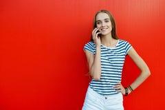 Lächelnde Frau mit einer Tasche vor der roten Wand Stockfotos