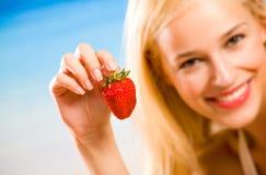 Lächelnde Frau mit Erdbeere Lizenzfreie Stockbilder