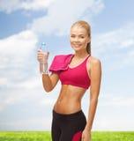 Lächelnde Frau mit Flasche des Wassers und des Tuches Stockbilder