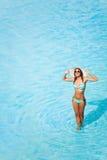 Lächelnde Frau mit Gläsern steht im blauen Wasser stockfotografie