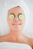 Lächelnde Frau mit Gurkescheiben auf dem Gesicht Stockfoto