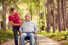 Lächelnde Frau mit ihrem behinderten Vater im Rollstuhl lizenzfreie stockfotos