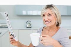 Lächelnde Frau mit Kaffeetasse und Zeitung in der Küche Lizenzfreies Stockfoto
