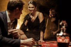 Lächelnde Frau mit Kasino brechen das Sitzen auf Pokertabelle und das Betrachten des Mannes ab Stockbild
