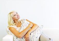 Lächelnde Frau mit Kissen auf Couch Lizenzfreies Stockbild
