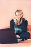 Lächelnde Frau mit Kopfhörern und Laptop stockfotos
