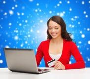 Lächelnde Frau mit Kreditkarte und Laptop Lizenzfreie Stockfotos