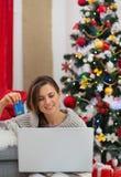Lächelnde Frau mit Laptop und Kreditkarte stockfotos