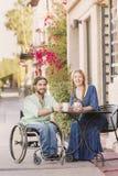 Lächelnde Frau mit Mann im Rollstuhl draußen Stockbild