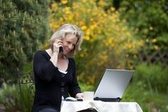 Lächelnde Frau mit Mobiltelefon und Laptop Stockfotos