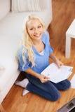 Lächelnde Frau mit Papieren, Laptop und Taschenrechner stockbilder