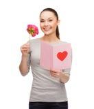 Lächelnde Frau mit Postkarte und Blume Lizenzfreie Stockfotos