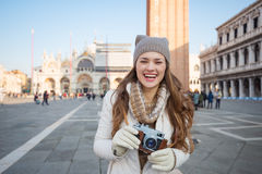 Lächelnde Frau mit Retro- Fotokamera auf Marktplatz San Marco Stockbild