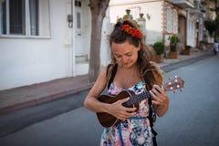 Lächelnde Frau mit Rosen in der Frisur hält im Handmusikinstrument lizenzfreie stockfotografie