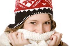 Lächelnde Frau mit Schutzkappenholdingschal über Mund Stockfoto