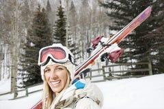 Lächelnde Frau mit Skis. Stockfotografie