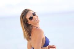 Lächelnde Frau mit Sonnenbrille auf dem Strand Stockfoto