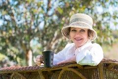 Lächelnde Frau mit Tasse Kaffee im Garten Stockbilder