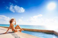 Lächelnde Frau mit weißem Hut, Sonnenbrillesitzen Lizenzfreies Stockfoto