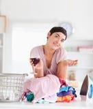 Lächelnde Frau mit Wein und ein Stapel von Kleidung Stockfoto