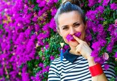 Lächelnde Frau nahe dem bunten magentaroten Blumenbett, das Spaßzeit hat lizenzfreie stockfotografie