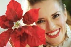 Lächelnde Frau nahe dem Weihnachtsbaum, der rote Poinsettia zeigt lizenzfreies stockbild